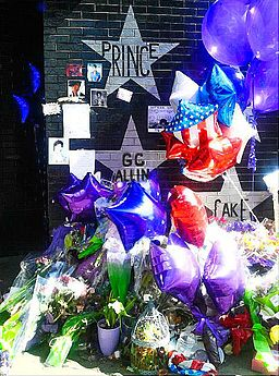 One of the many tribute memorials for Prince during this trecena in early 2016. Grieving fans left items such as CD's, purple balloons, cards, and love letters beneath the beloved artist's star on the front of a historic nightclub in Minneapolis after his death. Photo Credit: Hoff Entertainment [CC BY-SA 4.0], via Wikimedia Commons