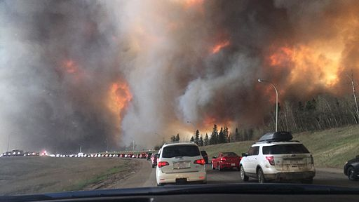Huge flames and heavy smoke in the Fort McMurray area as vehicles attempted to evacuate during this trecena in 2016. Photo credit: DarrenRD (Own work) [CC BY-SA 4.0], via Wikimedia Commons