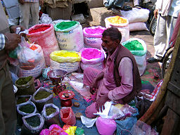 Selling coloured powders for the Holi festival, Delhi. Photo Credit: Eliza Raschke from Brisbane, Australia [CC BY 2.0], via Wikimedia Commons